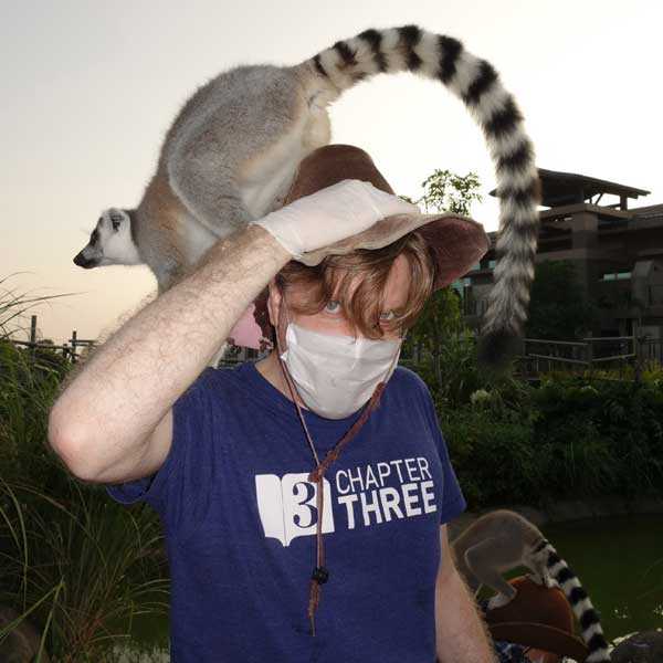 A photo of John with a lemur on his head